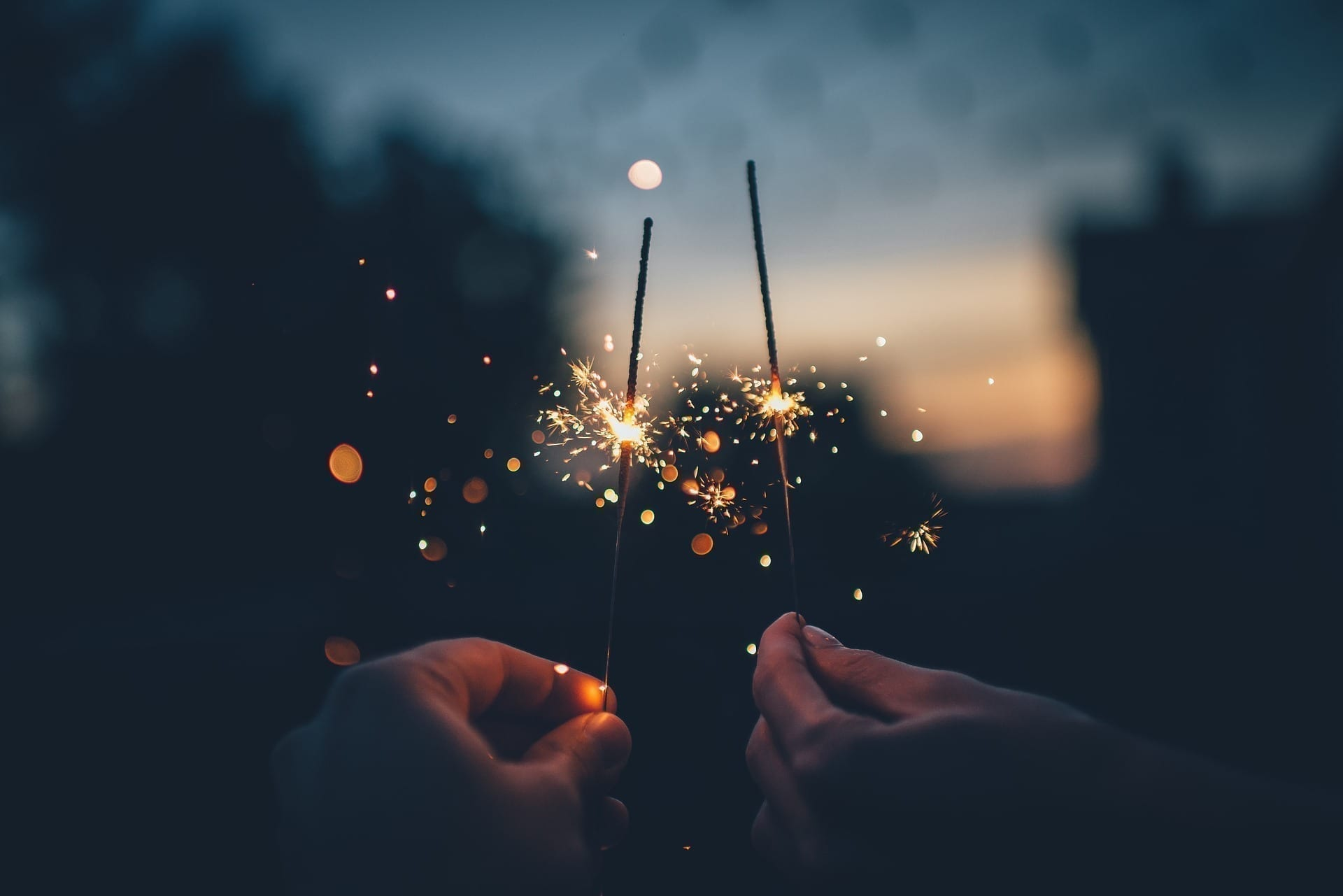 Two hands holding lit sparklers in front of a sunset