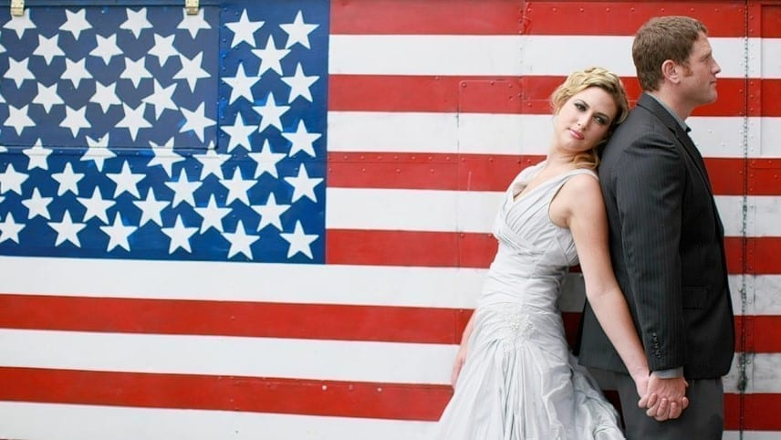 bride and groom standing in front of the american flag