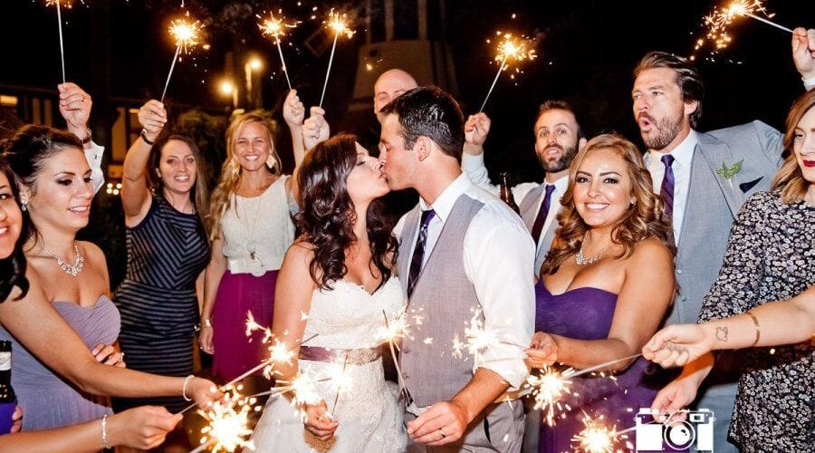Couple kissing in a sparkler exit by True Photography